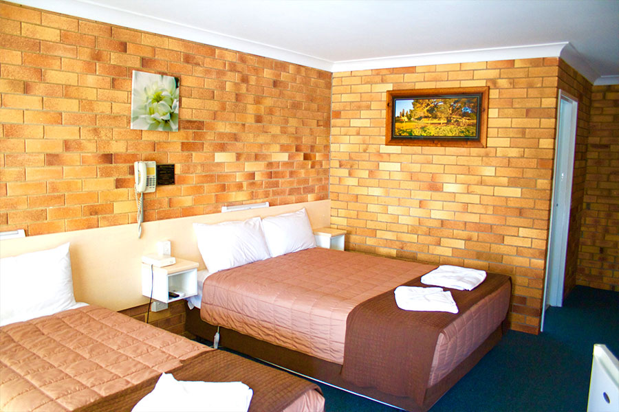 A room with brick walls, one queen bed and one single bed