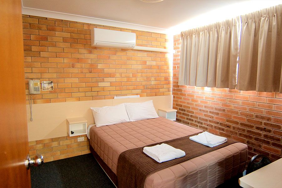 A bedroom with brown brick walls, that has one queen bed