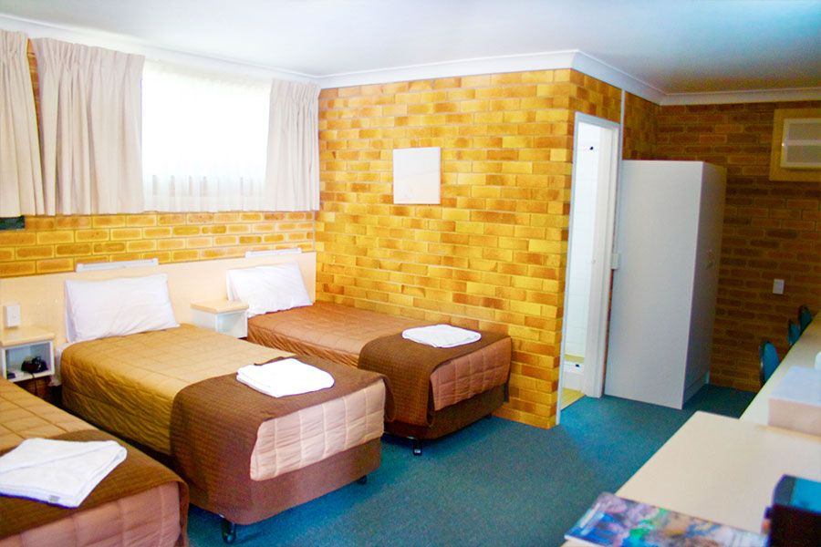 A room with brown walls and has one queen bed and two single beds, with an opened bathroom door
