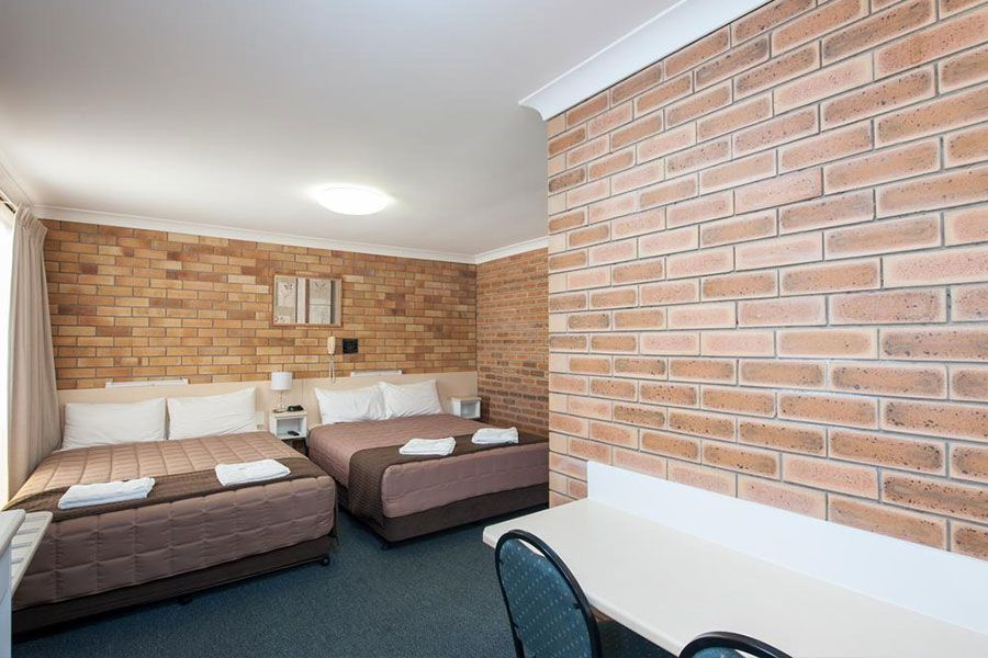 A room with brown brick walls and has two brown queen beds